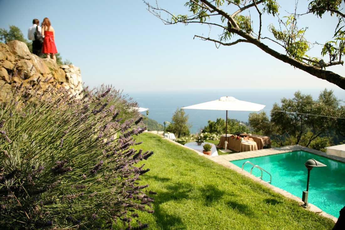 Eremo di Monterosso matrimonio estivo vista panoramica del giardino e della piscina allestiti con tavoli e ombrelloni