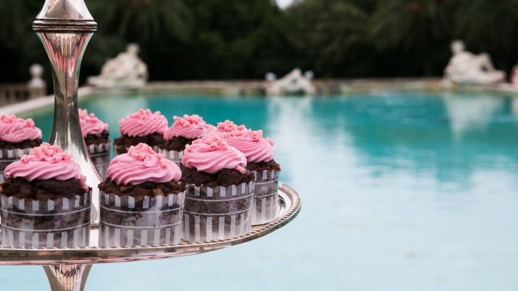 Villa Lo Zerbino matrimonio in giardino allestimento per la torta particolare cupcake al cioccolato su alzata in argento e piscina sullo sfondo