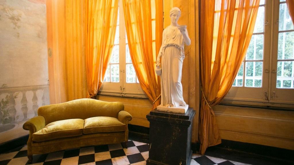Villa Lo Zerbino vista interno atrio del piano nobile divano verde tende arancioni e statua