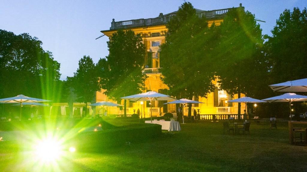 Villa Lo Zerbino matrimonio all'aperto giardino allestito per aperitivo estivo con tavoli e ombrelloni e villa illuminata
