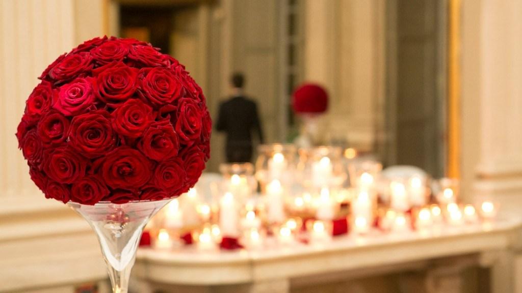 Villa Lo Zerbino evento al chiuso sala al piano terra particolare decorazione di fiori in rose rosse su vaso di vetro alto e vista candele davanti allo specchio