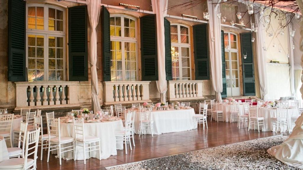 Villa Lo Zerbino matrimonio all'interno della tensostruttura allestita con tavoli con tovaglia bianca e centrotavola con fiori bianchi e rosa