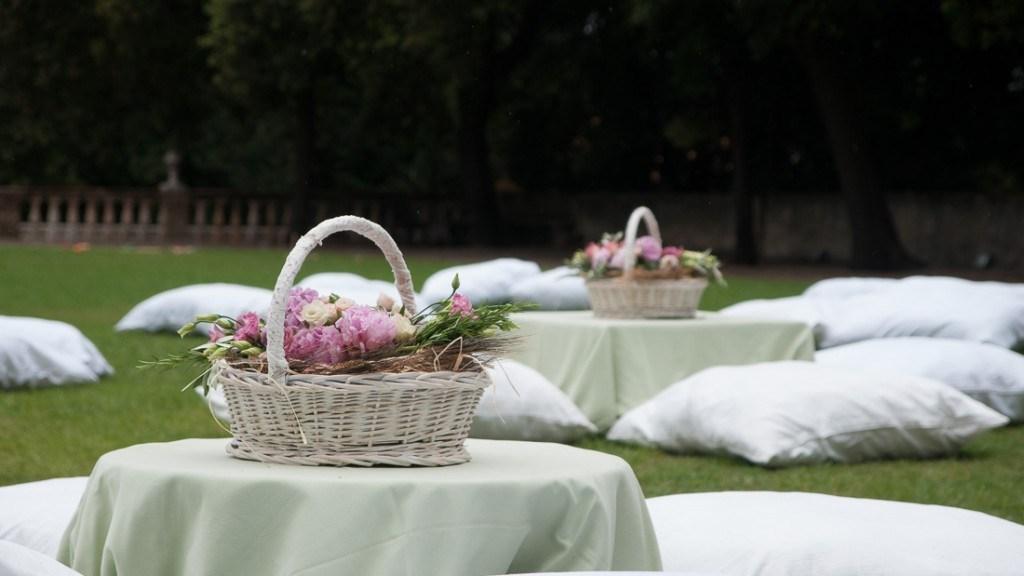 Villa Lo Zerbino matrimonio estivo all'aperto giardino allestito con tavolini bassi con tovaglia verde e cuscini bianchi centrotavola cestini in vimini con fiori