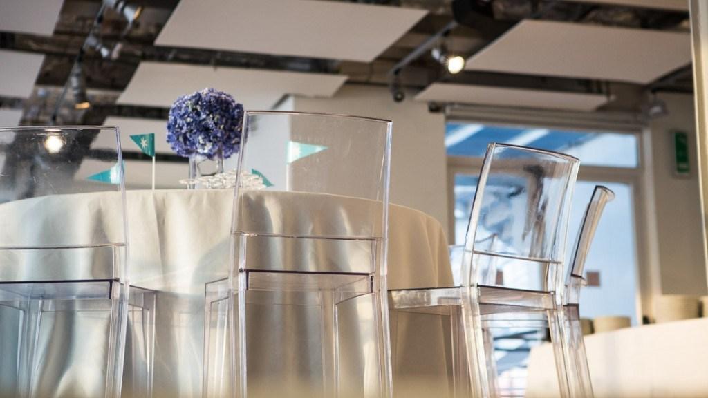 Acquario di Genova evento aziendale sala allestita con con tovaglie ecrù centro tavola di fiori e sedie trasparenti