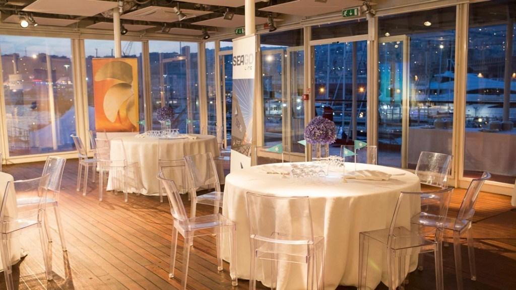 Acquario di Genova aperitivo aziendale sala allestita con tovaglie ecrù centrotavola con vaso e fiori viola e sedie trasparenti