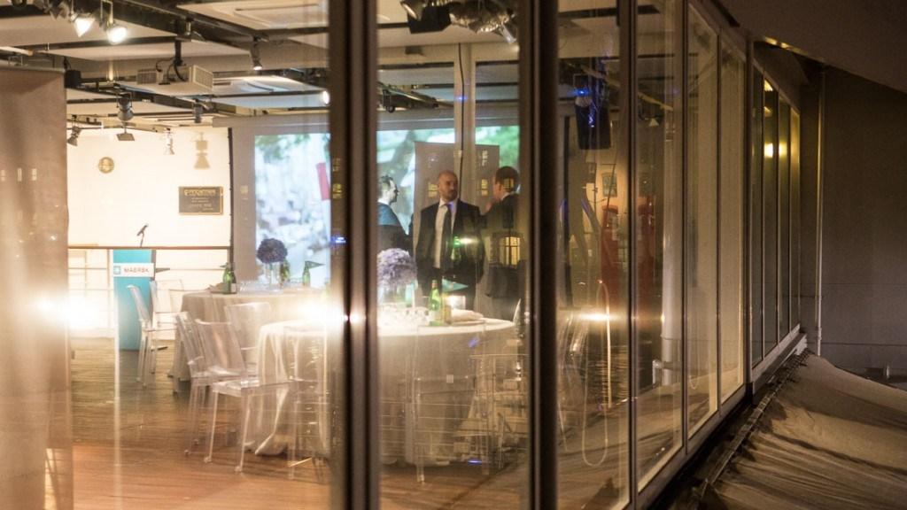 Acquario di Genova evento aziendale sala allestita con tavoli con tovaglie bianche con centro tavola di fiori e sedie trasparenti