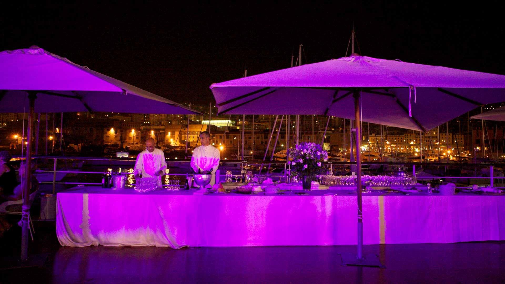 Acquario di Genova evento aziendale all'aperto vista del tavolo per il buffet degli apertivi allestito sulla tonda illuminato da luce viola