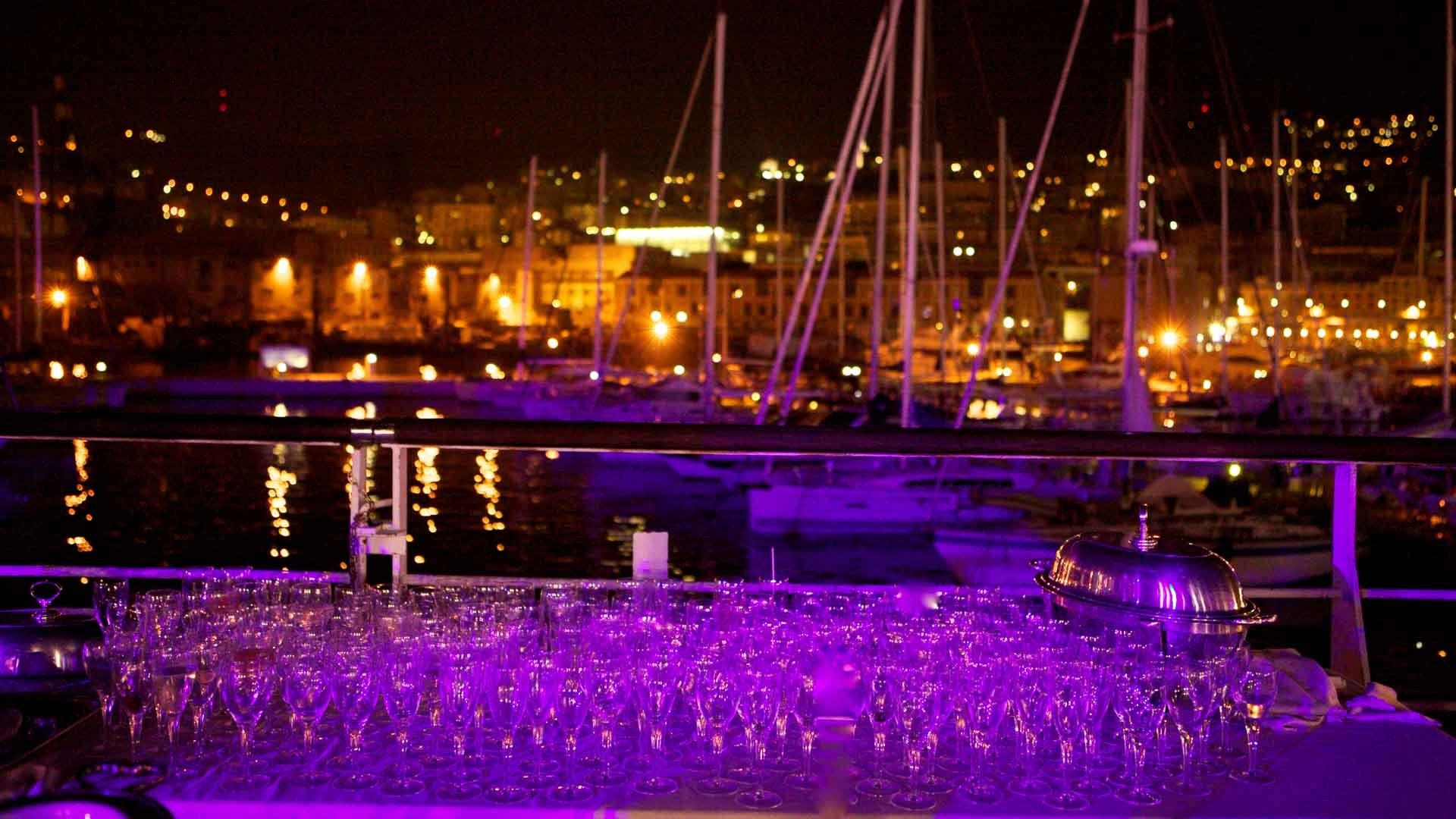 Acquario di Genova evento aziendale all'aperto particolare del tavolo per il buffet degli apertivi allestito sulla tonda con bicchieri che trasmettono luce viola