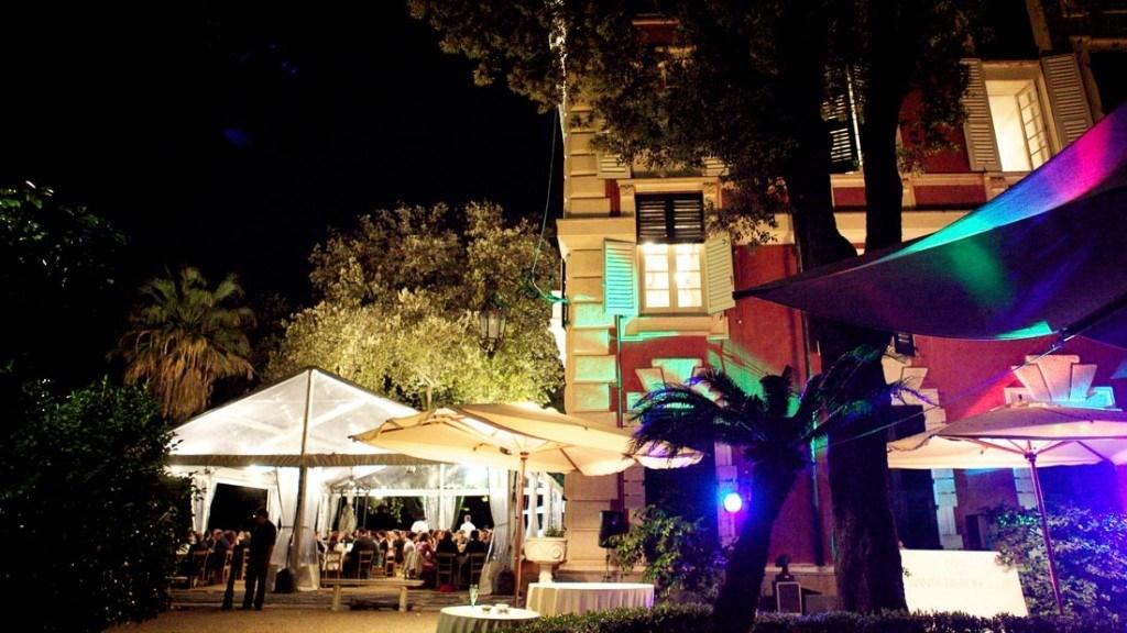 Villa Durazzo matrimonio estivo vista della tensostruttura allestita con tavoli per la cena e ombrelloni con luci colorate in giardino