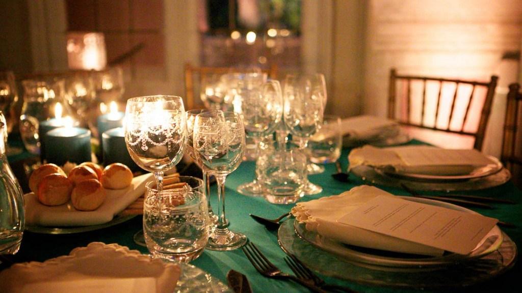 Villa Durazzo matrimonio elegante tavola allestita con piatti e bicchieri e candele illuminate color tiffany