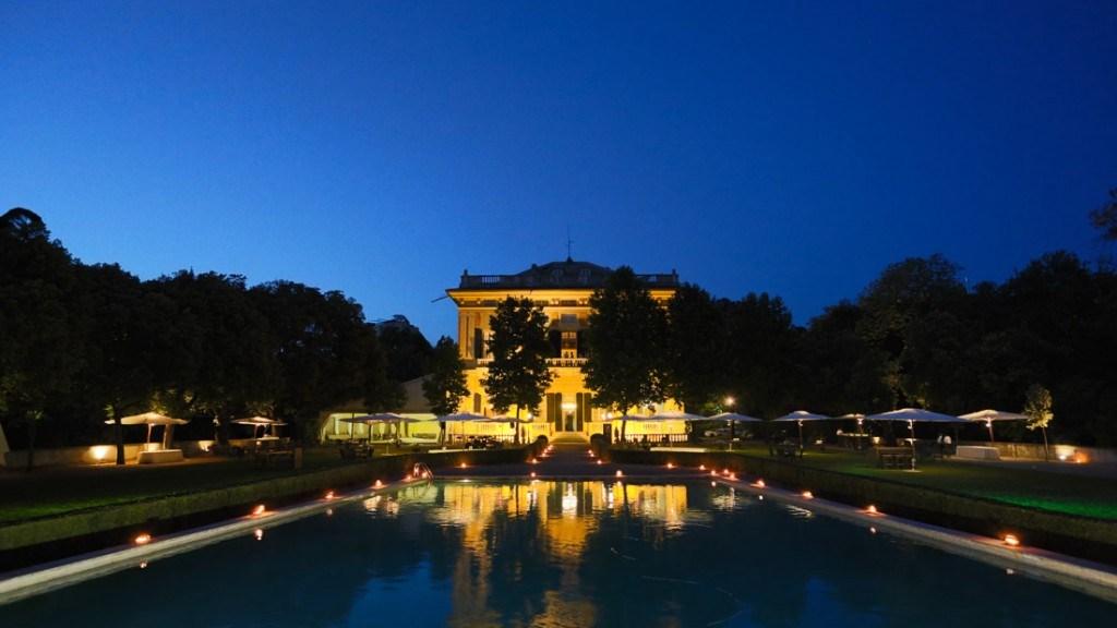 Villa Lo Zerbino evento all'aperto di sera con giardino villa e piscina illuminati con luci e candele giardino allestito con tavoli e ombrelloni