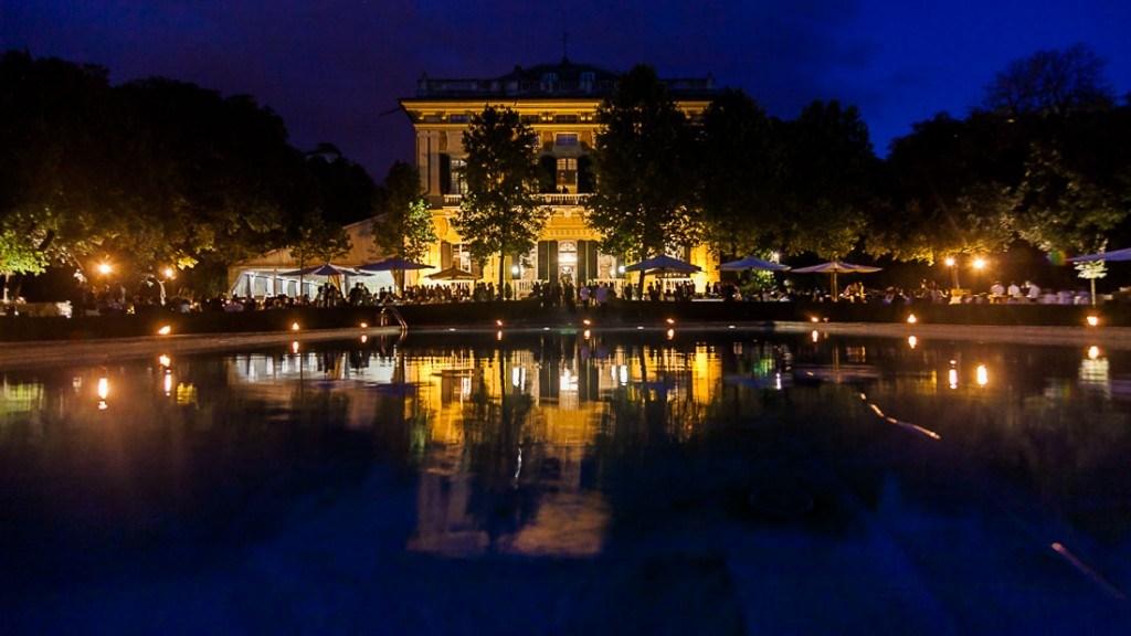 Villa Lo Zerbino evento all'aperto in giardino allestito con tavoli e isole per buffet illuminato con candele intorno alla piscina