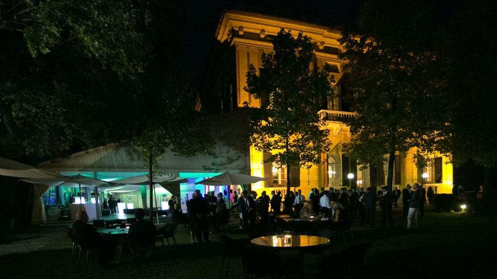 Villa Lo Zerbino evento aziendale all'aperto in giardino con tavoli e vista della tensostruttura illuminata ed allestita