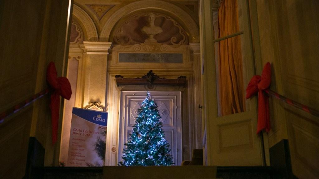 Villa Lo Zerbino vista interna dell'atrio al piano nobile allestito con con albero di natale illuminato e fiocchi rossi sul corrimano delle scale
