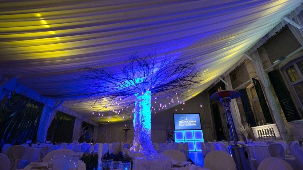 Villa Lo Zerbino cena aziendale allestita nella tensostruttura con tovaglie bianche e albero decorato con candele e luci blu
