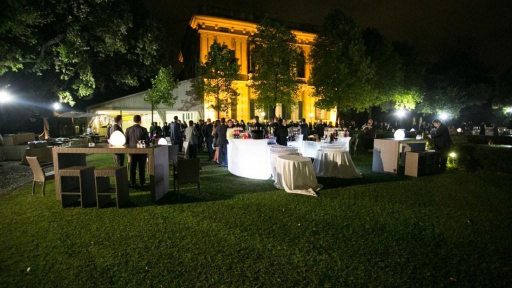 Villa Lo Zerbino facciata illuminata per cocktail aziendale all'aperto in giardino allestito con tavoli e bar