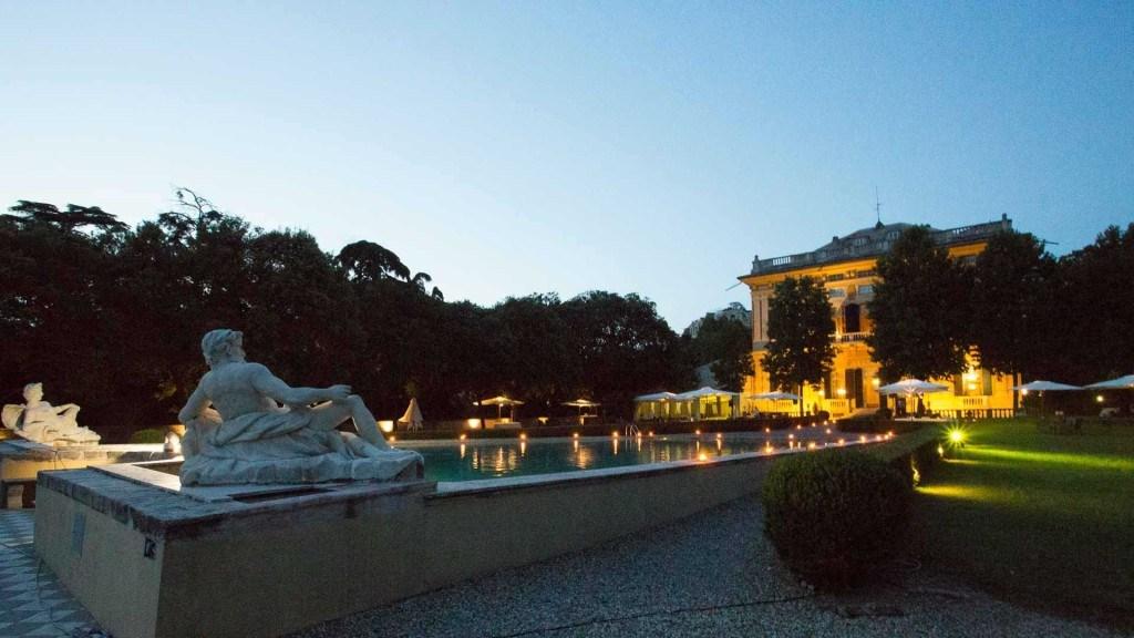 Villa Lo Zerbino vista panoramica del giardino allestito per evento estivo all'aperto con ombrelloni bianchi e tavoli piscina illuminata con luci e candele
