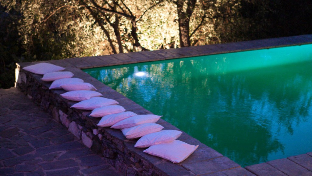 Eremo della maddalena matrimonio estivo bordo piscina allestito con cuscini bianchi