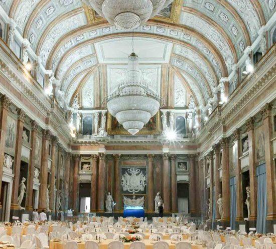 Palazzo Ducale sala allestita per evento aziendale con tavoli con tovaglie gialle e sedie rivestite di bianco