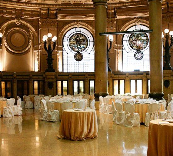 Palazzo della Borsa Genova sala allestita con tavoli tondi e sedie rivestite di color bianco con fiocco pesca in tinta con le tovaglie