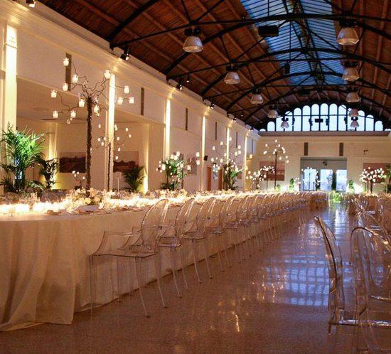 Stazione Marittima allestita per party aziendale tavolo rettangolare allestito con tovaglie ecru e sedie trasparenti e centrotavola fatto di candele accese e fiori