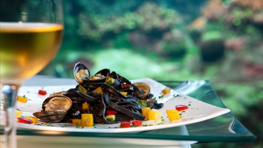 Acquario di Genova matrimoni elegante tavolo allestito per la cena con primo piatto posato su sottopiatto trasparente