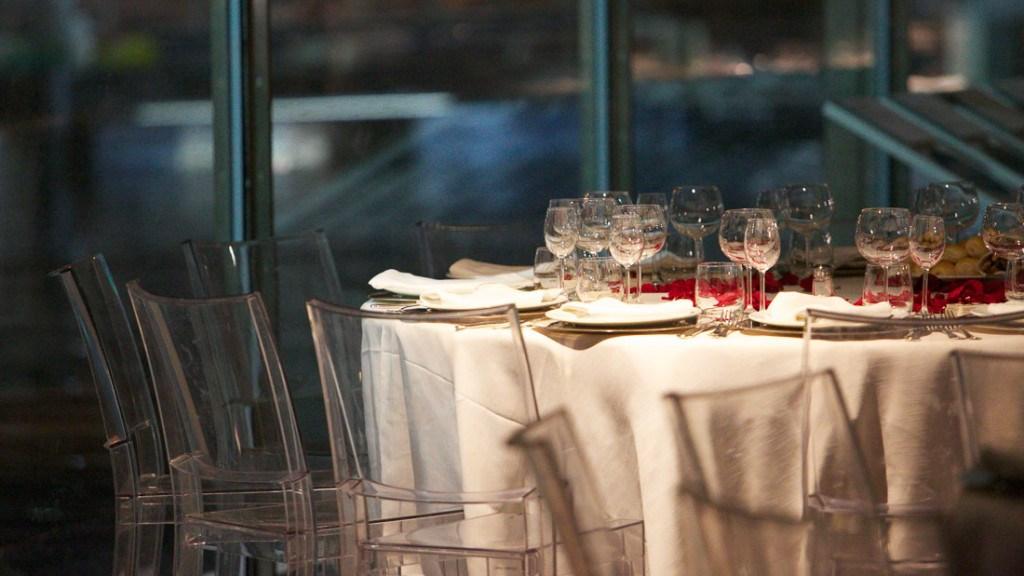 Acquario di Genova matrimonio elegante tavolo allestito con tovaglia bianca apparecchiato on sottopiatti argento e bicchieri con centrotavola di petali