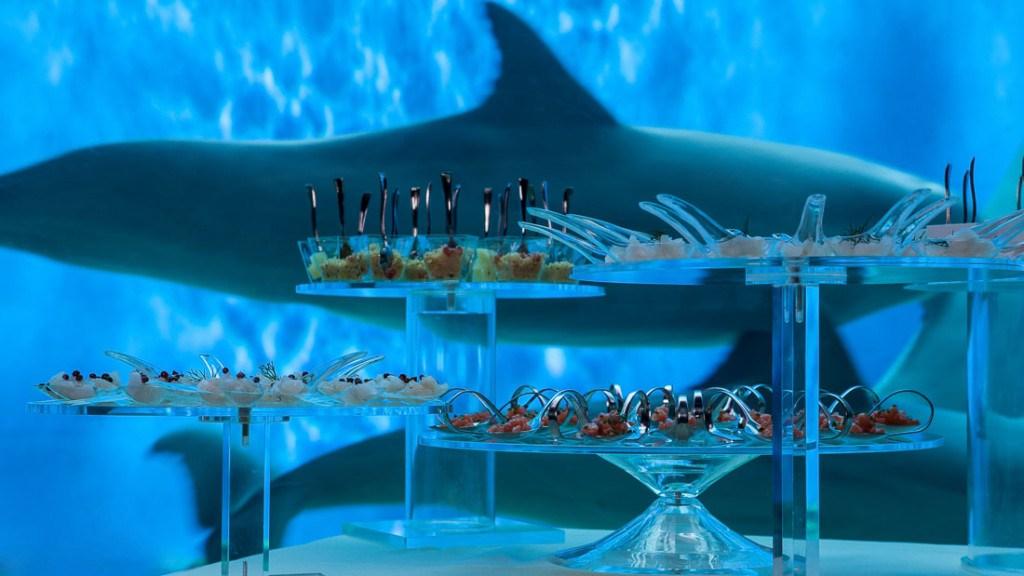 Acquario di Genova evento aziendale tavolo allestito per il buffet davanti alla vasca dei delfini tavolo allestito con alzate con bicchierini moscardini e cucchiaini con cibo ecosostenibile