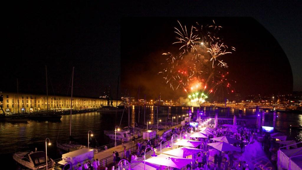 Acquario di Genova matrimonio elegante serale vista panoramica della tonda illuminata allestita con tavoli e ombrelloni luci colorate viola e fuochi di artificio sullo sfondo