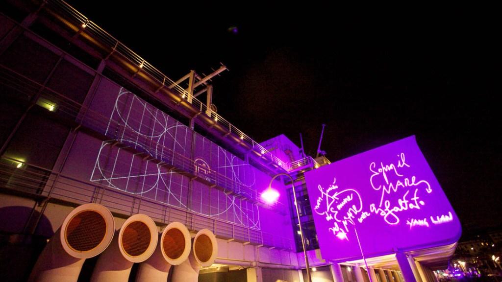 Acquario di Genova matrimonio serale vista panoramica facciata dell'acquario illuminata con luce viola e proiezione firme degli ospiti