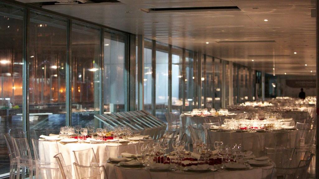 Acquario di Genova evento aziendale sala allestita con tavoli con tovaglia bianca sottopiatti in argento centrotavola con petali rossi e sedie trasparenti