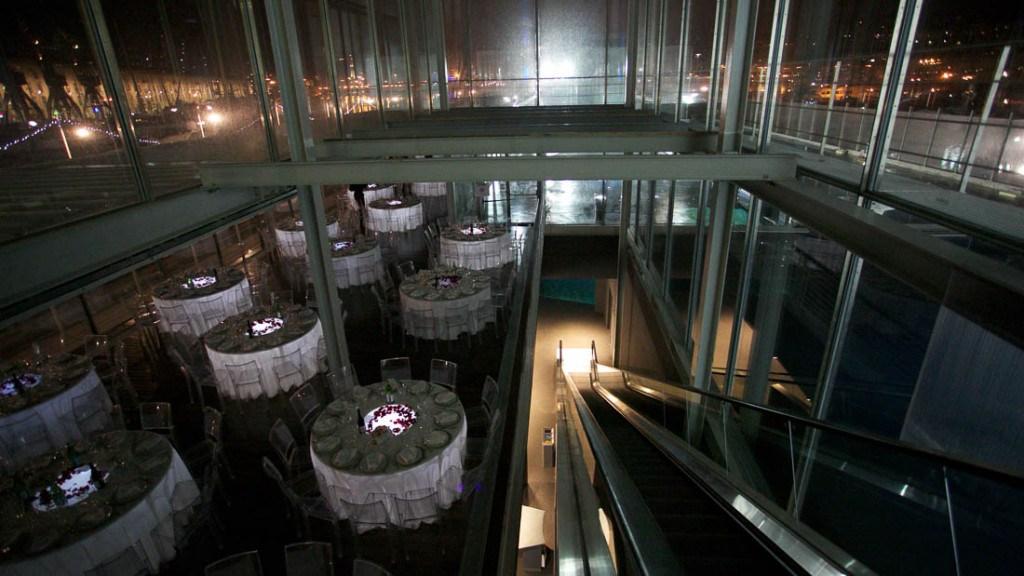 Acquario di Genova evento aziendale sala allestita con tavoli con tovaglia bianca sottopiatti in argento e sedie trasparenti