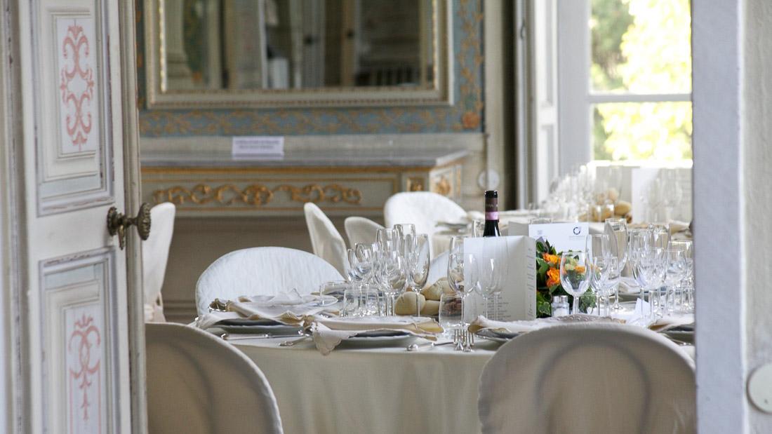 Villa Durazzo matrimonio elegante tavolo allestito per il pranzo con tovaglia e copri sedie bianchi centrotavola con fiori arancioni