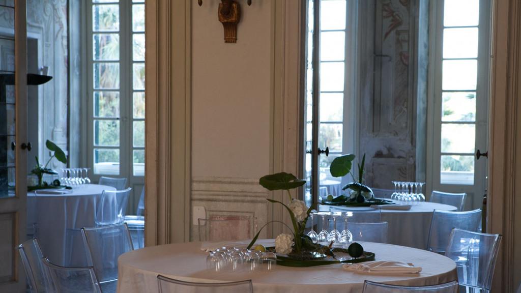 Villa Durazzo sala al primo piano allestita con tavoli preparati per l'aperitivo con centrotavola con fiori bianchi
