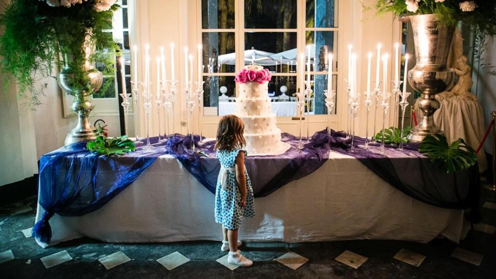 Villa Durazzo matrimonio elegante estivo piano terra tavolo allestito per il taglio della torta con candelabri alti e bambina che guarda la torta