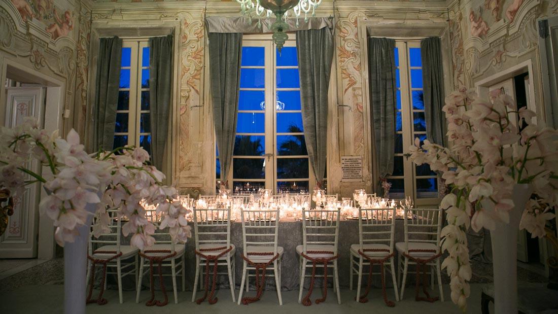 Villa Durazzo matrimonio estivo tavolo per la cena allestito con tovaglia grigia e candele e fiocchi sulle sedie bianche