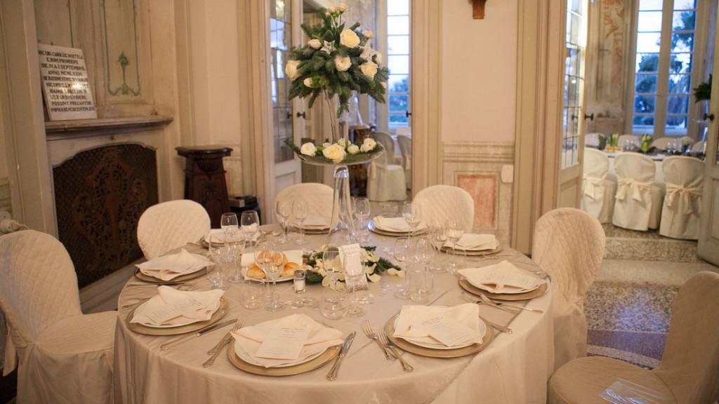Villa Durazzo matrimonio elegante sala allestita con tavoli con tovaglie bianche e coprisedie bianchi centrotavola di fiori e vasi trasparenti alti