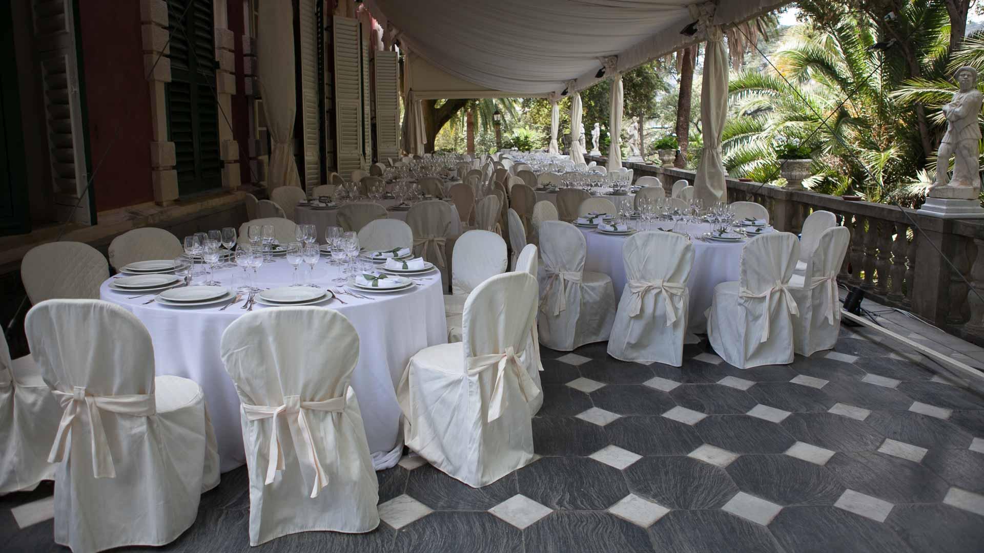 Villa Durazzo matrimonio estivo tensostruttura aperta allestita con tavoli preparati per il pranzo con tovaglie bianche e coprisedie con fiocco rosa.