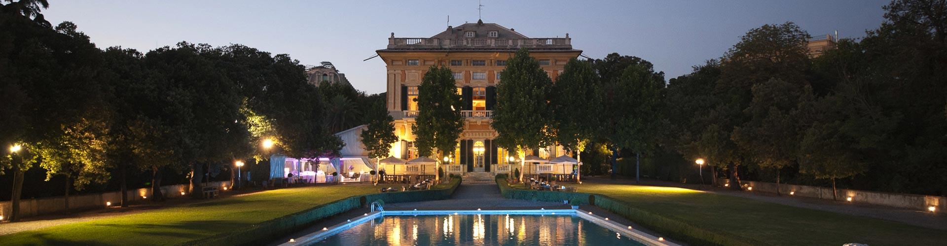 Villa Lo Zerbino vista notturna del giardino allestito con ombrelloni bianchi e tavoli e facciata della villa illuminata