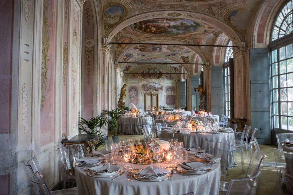 villa faraggiana sala delle stagioni allestita per matrimonio elegante tavoli con tovaglie beige e sedie trasparenti allestiti con centrotavola con specchi e fiori con candele