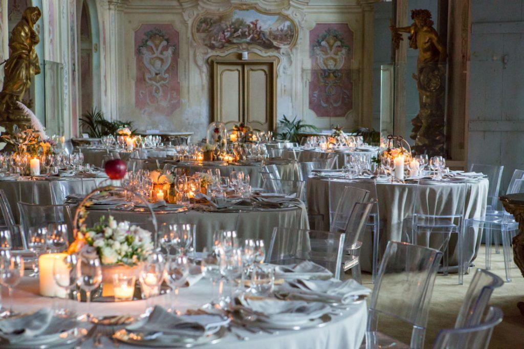 villa faraggiana sala delle stagioni allestita per matrimonio elegante tavoli con tovaglie beige e sedie trasparenti allestiti con centrotavola con fiori candele e mele