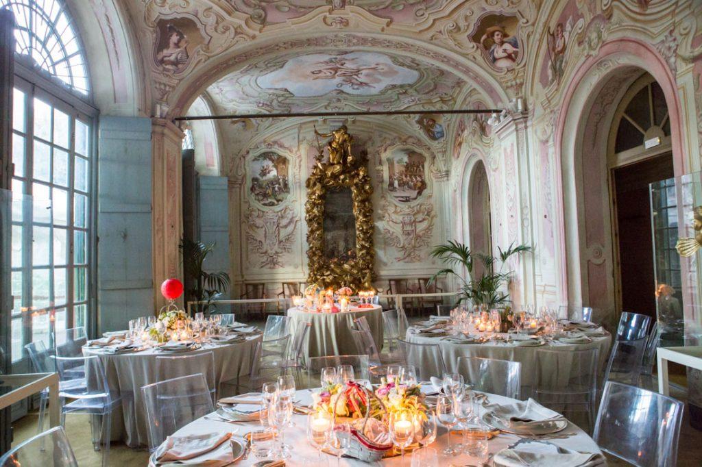 villa faraggiana sala delle stagioni allestita per matrimonio elegante tavoli con tovaglie beige e sedie trasparenti allestiti con centrotavola con fiori candele