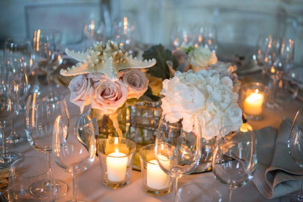 villa faraggiana matrimonio di sera tavolo allestito con centrotavola a specchio con vasi di fiori e candele bianche