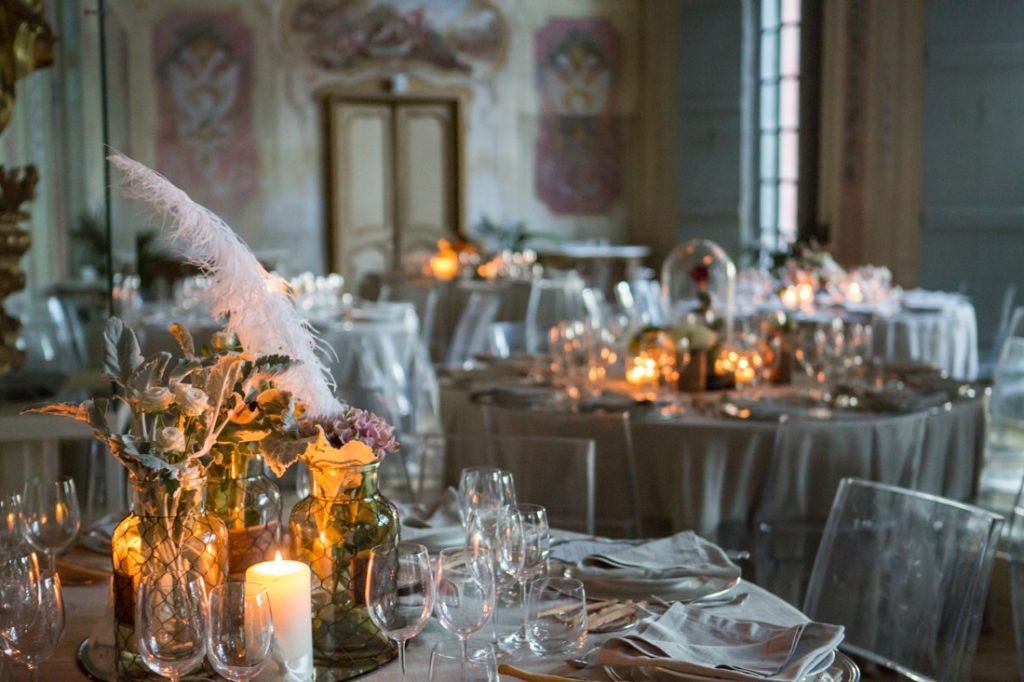 villa faraggiana matrimonio elegante serale sala allestita con tavoli con centrotavola con fiori e candele sedie trasparenti