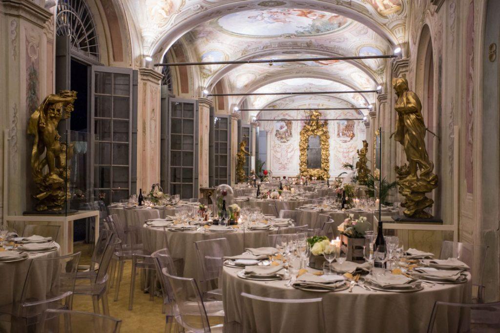 villa faraggiana sala delle stagioni allestita per matrimonio elegante tavoli con tovaglie beige e sedie trasparenti centrotavola con fiori