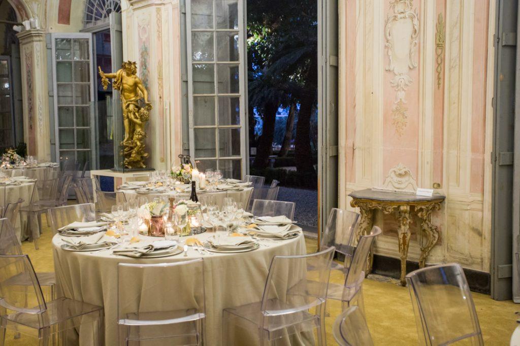 villa faraggiana matrimonio elegante sala delle stagioni affacciata sul giardino allestita con tavoli con tovaglie beige e sedie trasparenti centrotavola con fiori