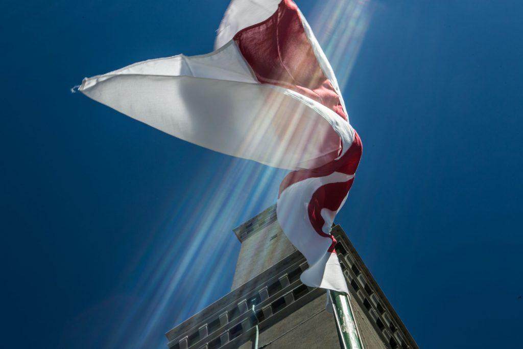 Lanterna di Genova vista della bandiera di Genova che sventola sotto la lanterna tagliata da un raggio di sole