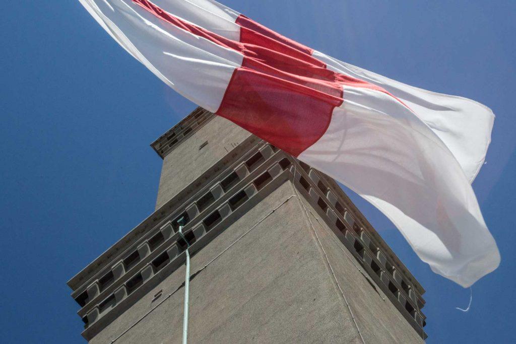 Lanterna di Genova vista della bandiera di Genova che sventola sotto la lanterna